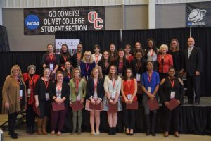 A group of 26 people stand on a stage, comprised of college leaders and students who have just completed the Women's Leadership Institute program.