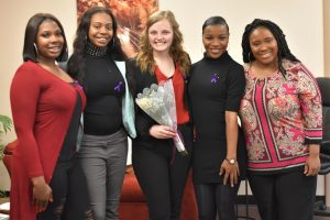 Senior Abby Smith (center) was awarded a yellow rose by the Golden Z Club on International Women's Day to acknowledge her support of women on campus.