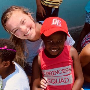 A member of the volleyball team with a child at Mama Rosie's Orphanage.